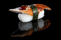 Nigiri σουσιών με το χέλι στο μαύρο υπόβαθρο με την αντανάκλαση Ιαπωνία Στοκ Εικόνες