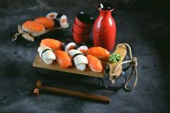 Nigiri и крены суш с семгами и зажаренным кальмаром на декоративных санях, предпосылке рождества Стоковые Фотографии RF