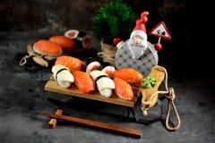Nigiri и крены суш с семгами и зажаренным кальмаром на декоративных санях, предпосылке рождества Стоковое Фото