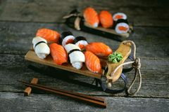 Nigiri и крены суш с семгами и зажаренным кальмаром на декоративных санях, предпосылке рождества Стоковое Изображение