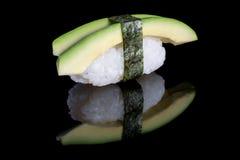 Nigiri del sushi con el aguacate en fondo negro con la reflexión J Imagenes de archivo