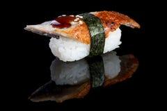 Nigiri del sushi con la anguila en fondo negro con la reflexión japón Imagenes de archivo