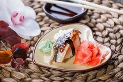 Nigiri determinado del sushi y rollos de sushi adornados con las flores en el fondo de bambú Foto de archivo
