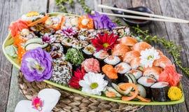 Nigiri determinado del sushi y rollos de sushi adornados con las flores en el fondo de bambú Cocina japonesa Imagen de archivo libre de regalías