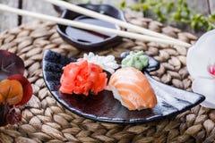 Nigiri determinado del sushi y rollos de sushi adornados con las flores en el fondo de bambú Cocina japonesa Foto de archivo libre de regalías