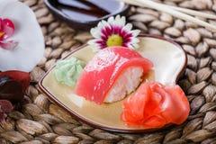Nigiri determinado del sushi y rollos de sushi adornados con las flores en el fondo de bambú Cocina japonesa Fotografía de archivo