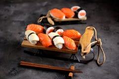 Nigiri e rolos do sushi com salmões e o calamar fritado no trenó decorativo, fundo do Natal Imagem de Stock