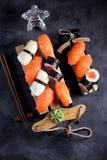Nigiri e rolos do sushi com salmões e o calamar fritado no trenó decorativo, fundo do Natal Fotos de Stock Royalty Free