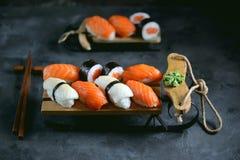 Nigiri e rolos do sushi com salmões e o calamar fritado no trenó decorativo, fundo do Natal Imagens de Stock Royalty Free