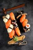 Nigiri e rolos do sushi com salmões e o calamar fritado no trenó decorativo, fundo do Natal Imagem de Stock Royalty Free