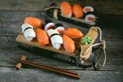 Nigiri e rolos do sushi com salmões e o calamar fritado no trenó decorativo, fundo do Natal Fotografia de Stock
