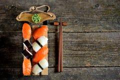 Nigiri e rolos do sushi com salmões e o calamar fritado no trenó decorativo, fundo do Natal Foto de Stock