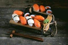 Nigiri e rolos do sushi com salmões e o calamar fritado no trenó decorativo, fundo do Natal Foto de Stock Royalty Free