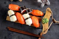 Nigiri e rotoli dei sushi con il salmone ed il calamaro fritto sulla slitta decorativa, fondo di natale Immagini Stock