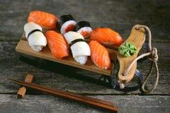 Nigiri e rotoli dei sushi con il salmone ed il calamaro fritto sulla slitta decorativa, fondo di natale Fotografie Stock