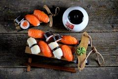 Nigiri e rotoli dei sushi con il salmone ed il calamaro fritto sulla slitta decorativa, fondo di natale Fotografia Stock