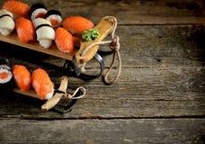 Nigiri e rotoli dei sushi con il salmone ed il calamaro fritto sulla slitta decorativa, fondo di natale Fotografia Stock Libera da Diritti