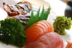 Nigiri Sushi. Fresh tuna, atlantic salmon and jumbo shrimp individually hand pressed with rice. Served with wasabi sauce. Shallow DOF royalty free stock image