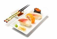 Nigiri sushi and chopsticks. Nigiri sushi variation with wasabi, ginger, caviar, tuna, heart-mussel, chopsticks, soy sauce on rectangular plates, isolated on Stock Images