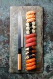 Nigiri Sushi and knife background. Nigiri Sushi and Japanese knife on stone slate background royalty free stock photo