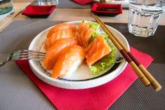 Nigiri sushi med laxen på en vit platta med pinnar och gaffeln Royaltyfri Bild