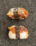 Nigiri-Sushi mit geräuchertem Aal und Meerespflanze Nori auf dunklem Hintergrund Lizenzfreies Stockfoto