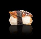 Nigiri-Sushi mit geräuchertem Aal und Meerespflanze Nori auf dunklem Hintergrund Stockfotos