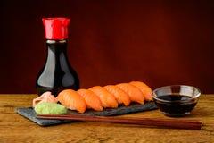 Nigiri-Sushi mit Lachsen, Sojasoße und Essstäbchen Lizenzfreie Stockfotografie