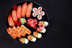 Nigiri sushi- och makirullar ställde in på den runda plattan arkivbild