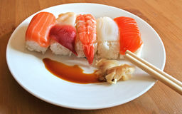 Nigiri sushi platter. A plate of mixed seafood nigiri sushi sits on a white plate with chopsticks, pickled ginger and soy sauce Stock Image