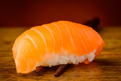 Nigiri sushi with salmon on chopsticks Stock Images