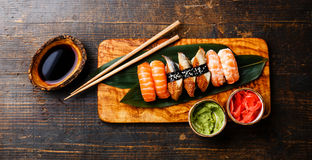 Nigiri Sushi Set on bamboo green leaf. On olive wood board with soy sauce on wooden background Royalty Free Stock Images
