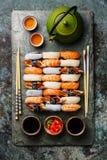 Nigiri sushi set for two and green tea. Nigiri sushi set for two on gray stone slate plate board and green tea Stock Image
