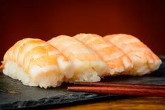 Nigiri sushi with shrimps. Closeup detail of nigiri sushi with shrimps and chopsticks Royalty Free Stock Images