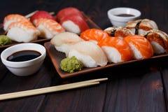 Nigirisushi met zalm, tandbaars, paling, tonijn en garnaal op klei p stock foto's