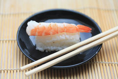 Nigirisushi, rolled rice and scrimp. A traditional Nigirisushi, made from cooked vinegared sushi rice and a scrimp topping. This sushi is served on a small black Stock Photography