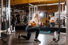 Nikła blond dziewczyna z długie włosy ubierającym w sportswear robi z powrotem kuca w nowożytnym gym obok lustra zdjęcia royalty free
