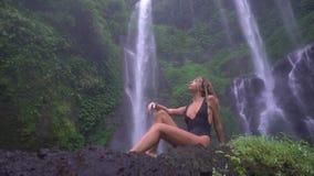 Nikła dorosła dziewczyna w czarnym kostiumu kąpielowym siedzi pod wielką tropikalną kaskadą, podziwia tropikalną naturę zdjęcie wideo