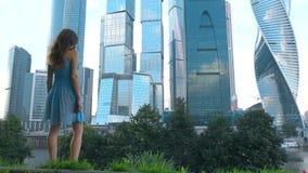 Nikła dziewczyna patrzeje nowożytnych drapacze chmur Moskwa miasto w błękit sukni, Rosja, 4K materiał filmowy zbiory wideo