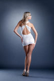 Nikła dziewczyna pozuje w krótkiej sukni kamera, z powrotem Obraz Stock