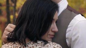Nikła kobieta w koronkowej sukni cuddles do mężczyzna w kostiumu, zwolnione tempo strzelanina w jesień parku zbiory wideo