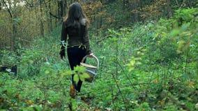 Nikła młoda kobieta w brown kurtki odprowadzeniu przez lasowego mienia kosz 4K steadicam strzał zdjęcie wideo