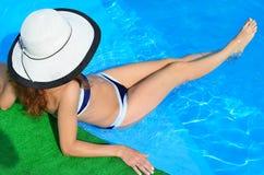Nikła młoda kobieta w kapeluszu siedzi na krawędzi basenu, płeć zdjęcie stock