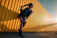 Nikła wysoka elegancka młoda dziewczyna w drelichowej kurtce, spódnicie i butach, Obrazy Stock