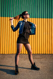 Nikła wysoka elegancka młoda dziewczyna w drelichowej kurtce, spódnicie i butach, Zdjęcia Royalty Free