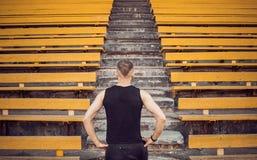 Nikły młody człowiek w czarnych sportswear stojakach przed schodka stadium stojakami przygotowywa dla akcji, kroczy zwycięstwo, w zdjęcia stock