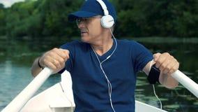 Nikły z włosami mężczyzna w białych hełmofonach, błękitnej nakrętce, koszulce i szkłach, wiosłuje wiosła na białej łodzi na zbiory wideo