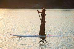 Nikła dziewczyna dalej stoi up paddleboard na zmierzchu tle SUP02 Obrazy Royalty Free