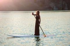 Nikła dziewczyna dalej stoi up paddleboard na zmierzchu tle SUP01 Obrazy Royalty Free