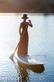 Nikła dziewczyna dalej stoi up paddleboard na zmierzchu tle SUP03 Zdjęcie Royalty Free